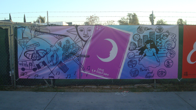 Banner on fence at a construction site on First Street. Art by Gabriella Claro, Salma Sosa, and Tatei Torres Thomas.