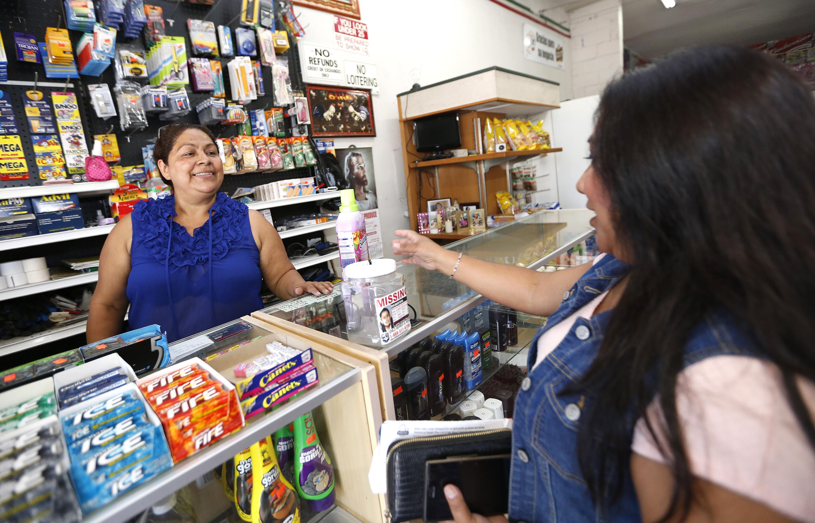 """Maria Ramirez , dueña de Ok Market, habla con Elvira Barrales. """"Agarramos la tiendita en un mal momento, pero es la inversión de mi hermano y aquí estamos, tenemos que seguir"""", asegura. (Aurelia Ventura/ La Opinion)"""