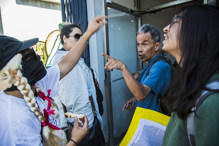 A customer argues with anti-gentrification protesters at the entrance to Weird Wave Coffee on Saturday