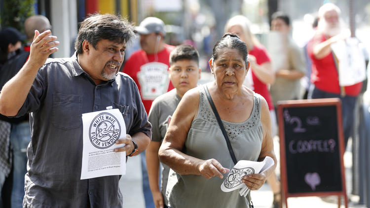 "Leonardo Vilchis, left, hands out fliers against Weird Wave Coffee in Boyle Heights in June. ""There is a trend of people being pushed out,"" Vilchis said. (Gary Coronado / Los Angeles Times)"