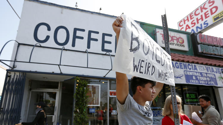 Opponents of Weird Wave Coffee in Boyle Heights demonstrate along East Cesar Chavez Avenue in June. (Gary Coronado / Los Angeles Times)