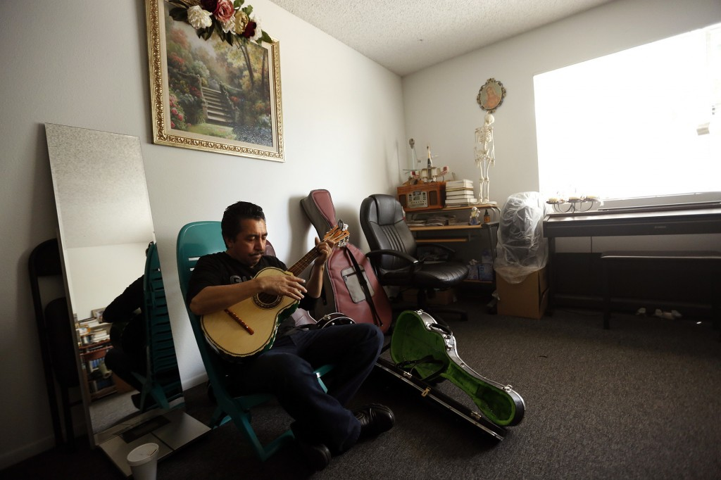 Mariachi performer Luis Valdivia practices in his apartment in Boyle Heights. Valdivia and his brother, Enrique, face eviction because they are unable to keep up with an 80% rise in rent. (Genaro Molina / Los Angeles Times)