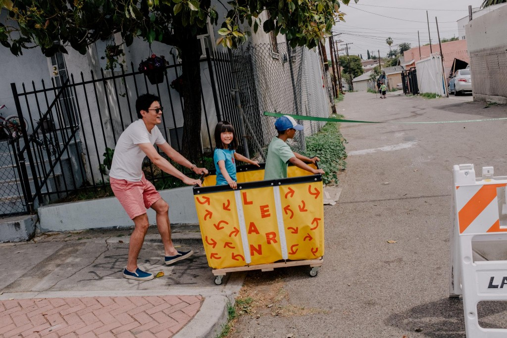 Children take a ride during a play streets event earlier this month.CreditColey Brown for The New York Times